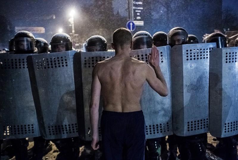 Участник акции протеста и сотрудники спецподразделения милиции «Беркут» на улице Грушевского в Киеве.
