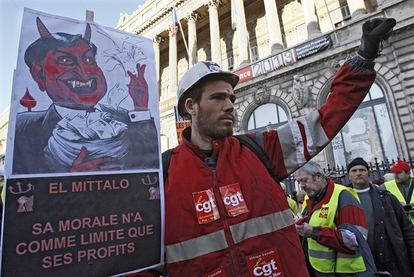 "An Arcelor Mittal worker holds a sign which depicts France's President Nicolas Sarkozy as the devil holding a bag of money and reads: 'The Mittal Devil - His Morals are only Limited by His Profits"", during a protest march in Marseille, January 29, 2009. France's eight labour unions have called on public and private sector workers to go on strike on Thursday to demand more action from government and companies to protect jobs and salaries. REUTERS/Jean-Paul Pelissier (FRANCE)"