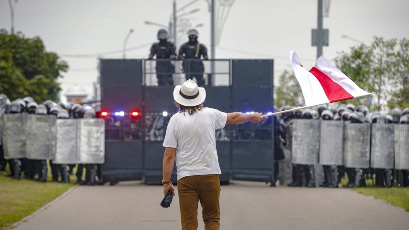 A man waves a historical Belarus flag in front of a riot police blockade during a protest in Minsk, Belarus, Sunday, Aug. 23, 2020. Demonstrators are taking to the streets of the Belarusian capital and other cities, keeping up their push for the resignation of the nation's authoritarian leader, president Alexander Lukashenko, in a massive outburst of dissent that has shaken the country since dubious presidential elections two weeks ago.(AP Photo/Sergei Grits)